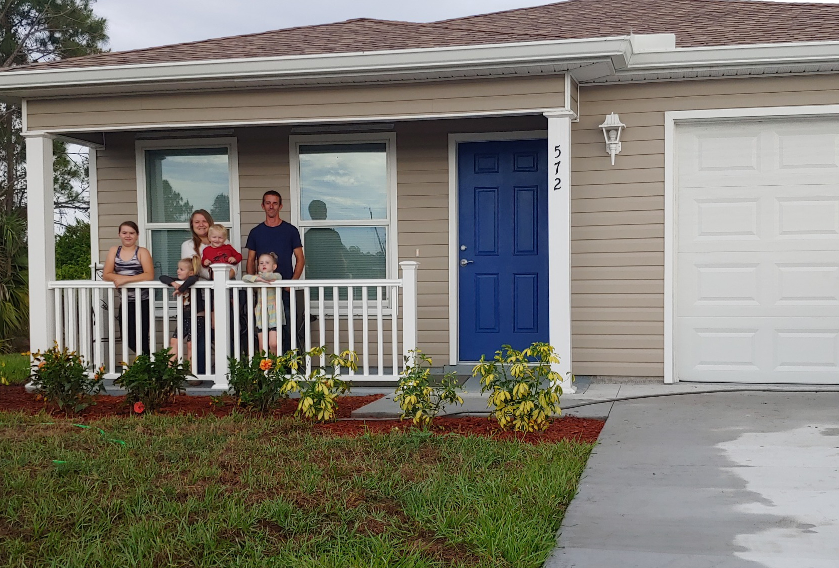 Habitat family on the front porch of their Habitat home, Habitat for humanity of Lee and Hendry Counties